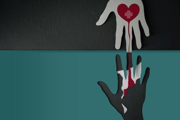 Concetto di donazione di sangue. aiuto, cura, amore, sostegno. carta tagliata a forma di mano appesa al muro