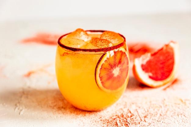 Cocktail margarita all'arancia rossa in un bicchiere vecchio stile con paprika affumicata sul bordo, pompelmo rosa.