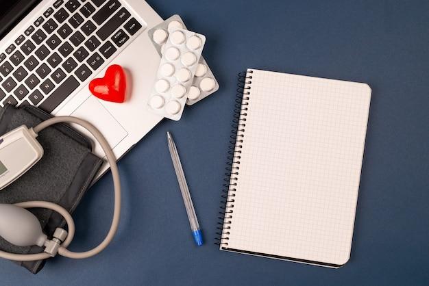 Misuratore di pressione sanguigna sul portatile con cuore rosso e pillole su sfondo blu scuro. blocco note di carta concetto di cardiologia.