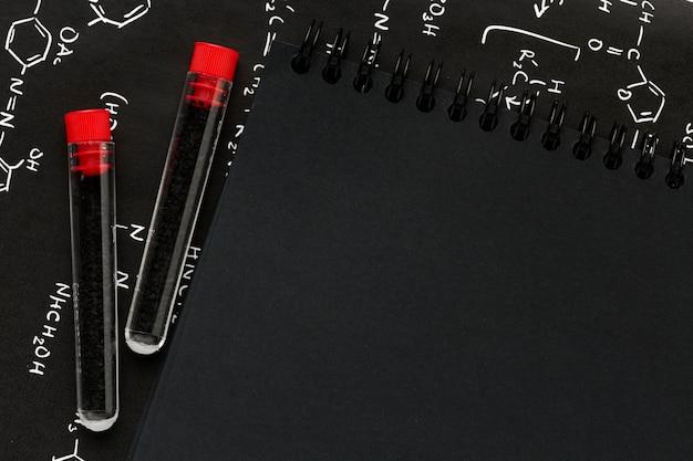 Campioni di sangue sulle formule chimiche accanto al blocco note nero vuoto