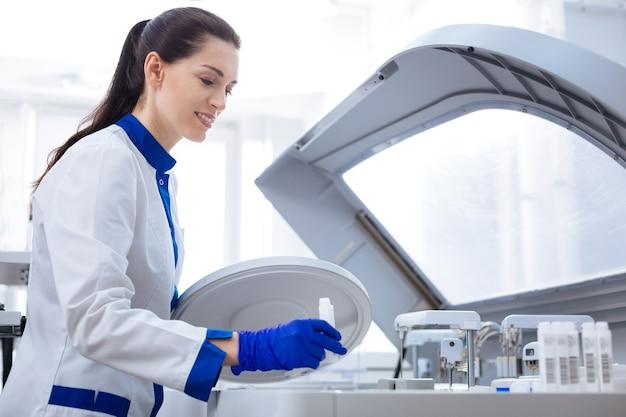 Separazione del sangue. assistente di laboratorio professionale concentrato guardando in basso tenendo il coperchio e preparandosi a posizionare un contenitore speciale