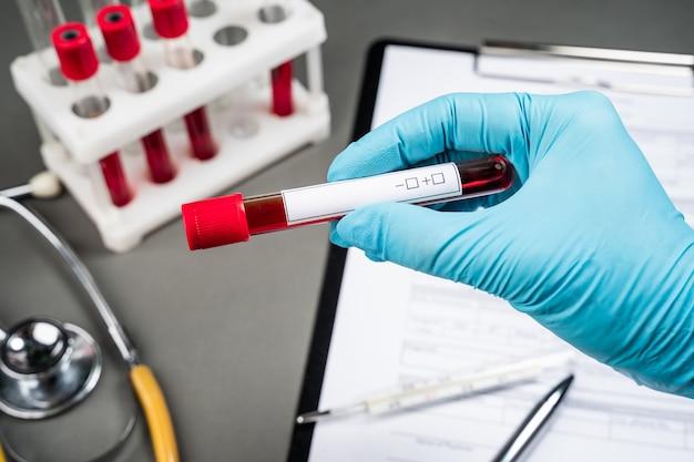 Fiala di sangue con campione di sangue sul modulo di prova
