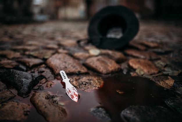 Arma del delitto insanguinata, pozza di sangue e cappello della vittima attacco di rapina per strada. concetto di criminalità
