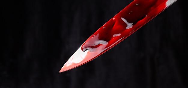 Un coltello insanguinato su sfondo nero. il concetto di omicidio, crimine.