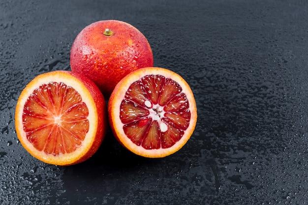 Arance insanguinate intere e tagliate a metà su lavagna nera con gocce d'acqua, frutta arancione siciliana rossa, vista dall'alto, spazio libero per il testo