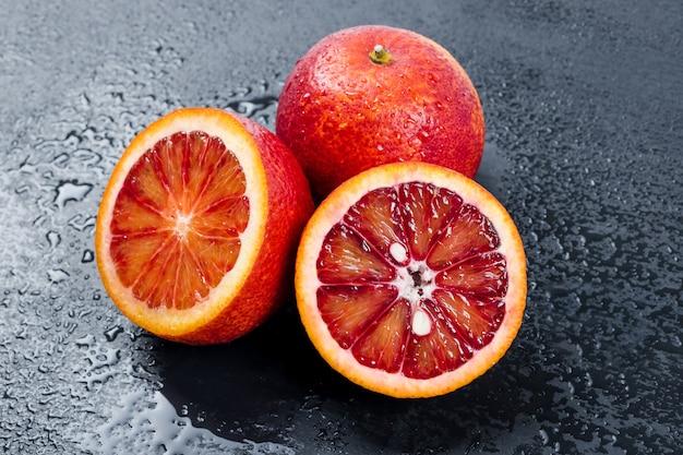 Arance insanguinate intere e tagliate a metà su tavola di ardesia nera con gocce d'acqua, frutta arancia rossa di sicilia.