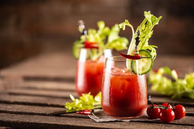 Cocktail bloody o virgin mary servito in tazza con coste di sedano e pomodorini.
