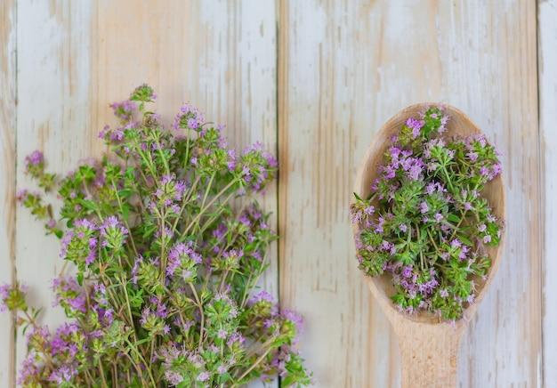 Timo di fioritura su un fondo di legno bianco. spezie, condimenti, erbe medicinali.
