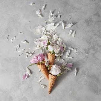 Fioritura di pioni bianchi e rosa, boccioli, foglia verde in un coni di cialda con petali su una pietra grigia sullo sfondo,