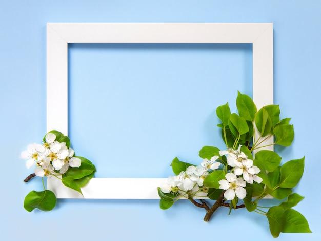 Ramo di melo in fiore accanto a una cornice bianca su sfondo blu. umore primaverile. disposizione piana, disposizione. carta o cornice pasquale.