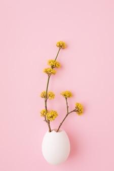 Rami in fiore in guscio d'uovo bianco su sfondo rosa. giorno di pasqua, concetto di primavera.
