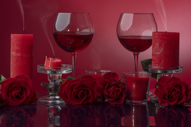 Candele rosse spente in bicchieri candelieri trasparenti con vino circondato da rose