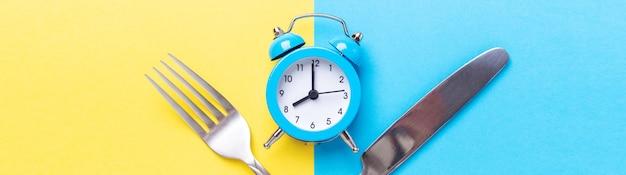 Sveglia blu, forchetta, coltello su sfondo di carta colorata. concetto di digiuno intermittente. banner orizzontale - immagine