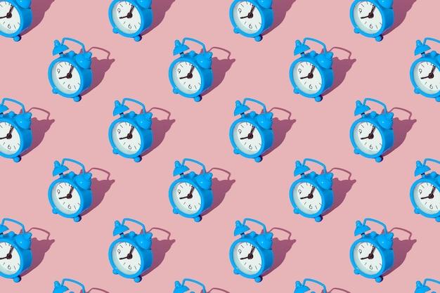 Sveglia blu su una superficie rosa