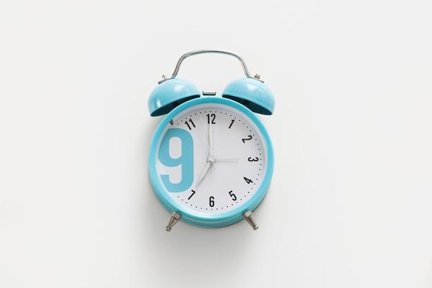 Sveglia blu su sfondo bianco. mattina, è ora di svegliarsi.
