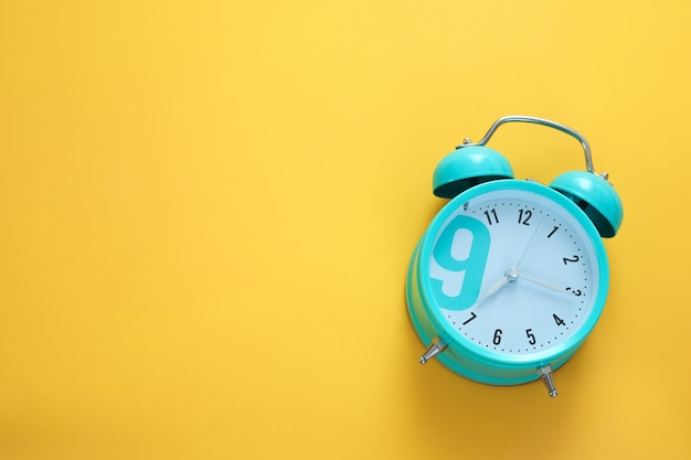 Sveglia blu su sfondo giallo. mattina, è ora di svegliarsi. spazio libero, copia spazio.