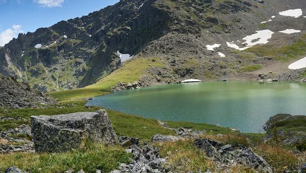 Lago alpino blu formato da un ghiacciaio in cima a una montagna. altai russia