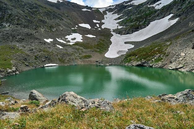 Lago alpino blu formato da un ghiacciaio in cima a una montagna.