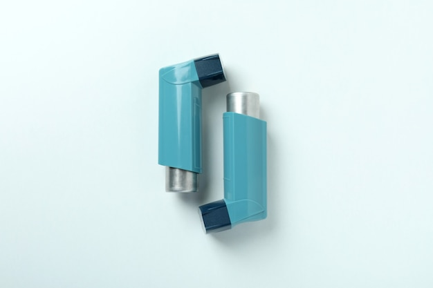 Inalatori per l'asma blu su sfondo bianco, vista dall'alto