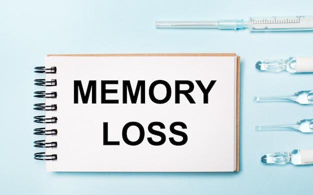 Su uno sfondo blu una fiala con medicinali e un taccuino con il testo perdita di memoria. concetto medico