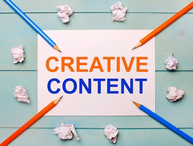 Su uno sfondo blu - matite nere e arancioni, fogli di carta stropicciati bianchi e un foglio di carta bianco con il testo contenuto creativo