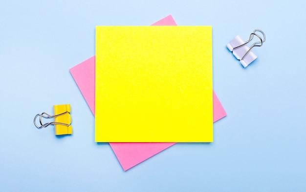 Lo sfondo blu ha clip gialle e bianche, adesivi per note rosa e gialli con spazio per inserire testo. modello