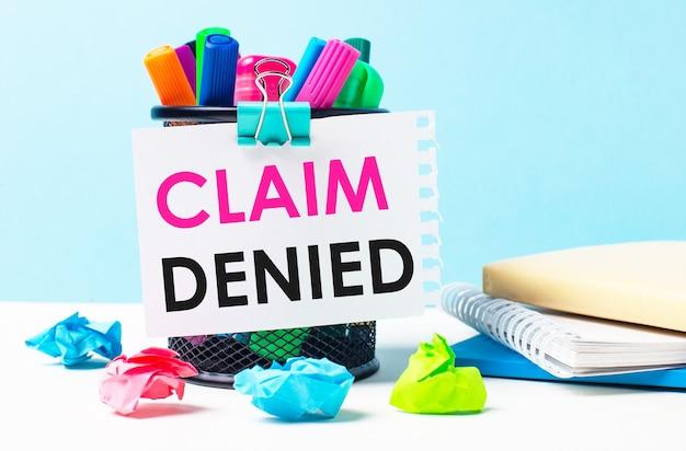 Su uno sfondo blu - un supporto con pennarelli luminosi, taccuini e pezzi di carta stropicciati multicolori. un foglio di carta con il testo claim denied.