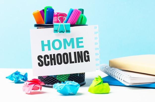 Su uno sfondo blu - un supporto con pennarelli luminosi, taccuini e pezzi di carta stropicciati multicolori. un foglio di carta con il testo scuola a casa.