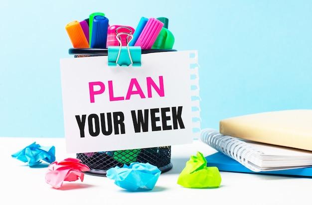 Su uno sfondo blu - un supporto con pennarelli luminosi, taccuini e pezzi di carta stropicciati multicolori. un foglio di carta con il testo pianifica la tua settimana.