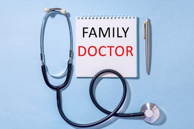 Su uno sfondo blu stetoscopio con blocco note e testo penna medico di famiglia