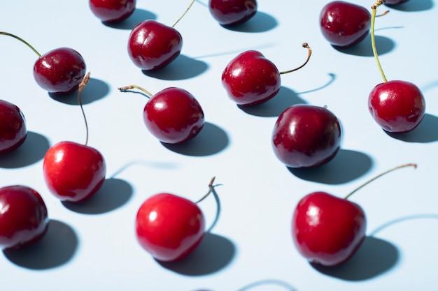 Sfondo blu con ciliegie rosse da vicino