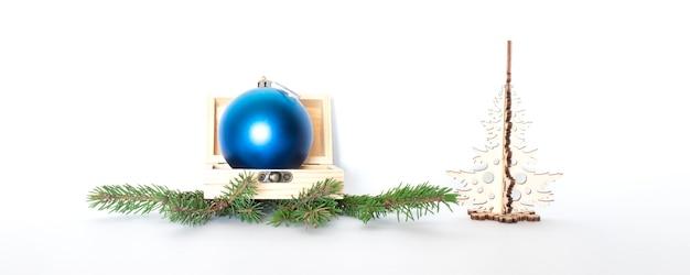 Sfera blu in scatola di legno che si trova sui rami di un albero di natale e di un albero di natale di legno.
