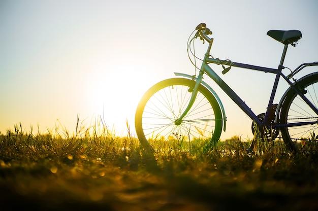 La bici blu è sulla spiaggia al lago al bel tramonto. romantico giro in bicicletta nella natura.