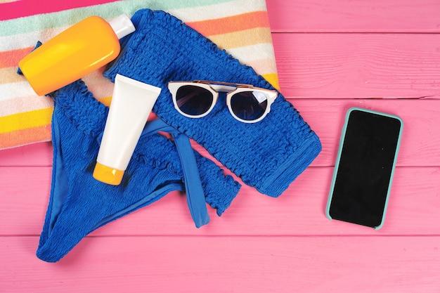 Bikini blu con bottiglia di crema solare su fondo di legno rosa brillante
