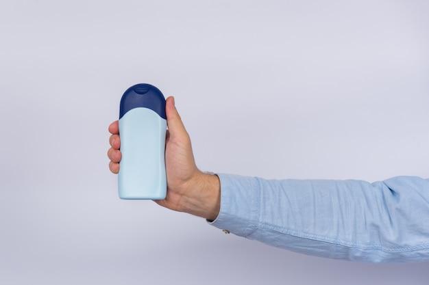 Bottiglia blu di sciampo o di lozione in mano maschio su bianco
