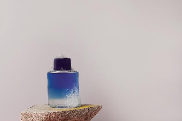 Flacone blu con dopobarba o lozione prebarba con bagnoschiuma che rimane sulla pietra