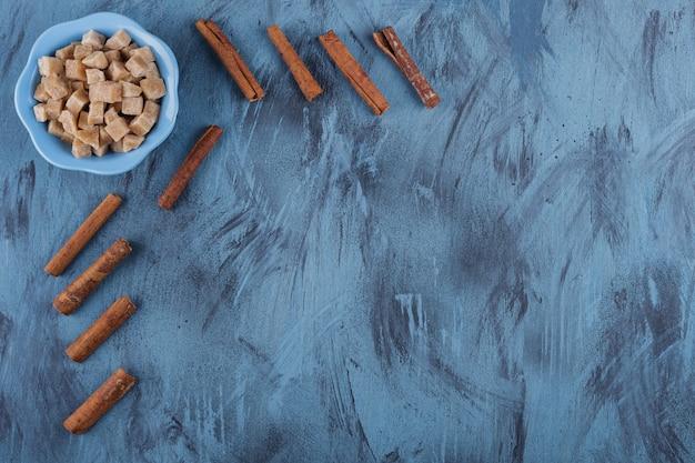 Ciotola blu di cubetti di zucchero di canna e bastoncini di cannella sulla superficie blu.