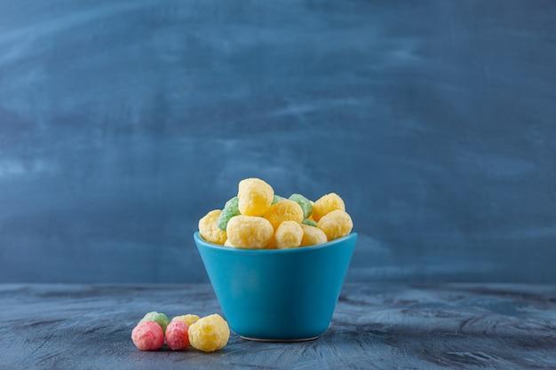 Ciotola blu piena di palline di cereali colorate su sfondo blu.