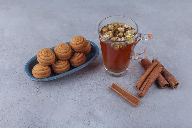 Ciotola blu di mini torte alla cannella con un bicchiere di tè sulla pietra.