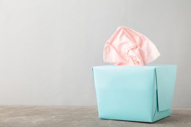Scatola blu con fazzoletti di carta su sfondo grigio