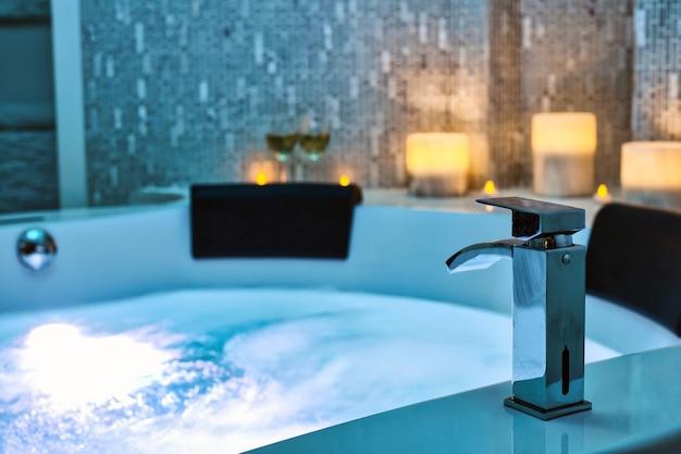 Acqua blu gorgogliante nella vasca idromassaggio close-up rubinetto decorato con candele sullo sfondo,
