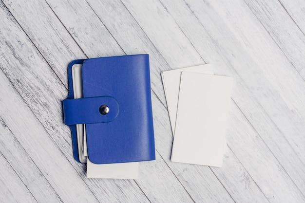 Porta biglietti da visita blu con carta intestata su una vista dall'alto di un tavolo in legno