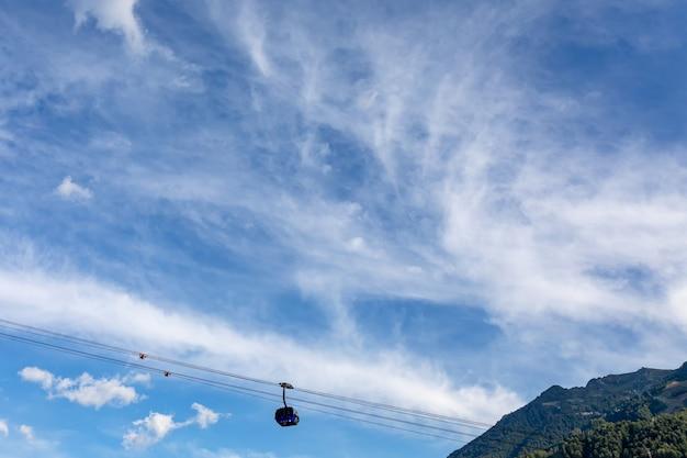 Funivia blu sopra le nuvole contro il cielo estivo con cirri