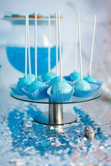La torta blu si apre sul panno d'argento. tema del tempo di mare sul candy bar della festa.