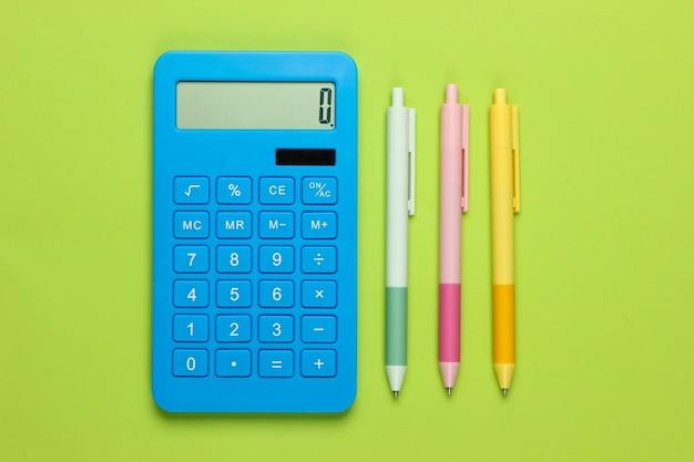 Calcolatrice blu con penne colorate su un verde. strumenti di office. economista