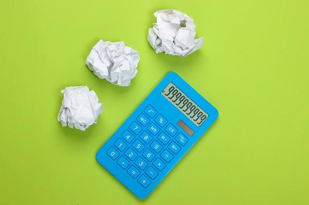 Calcolatrice blu con palline di carta sgualcite sul verde