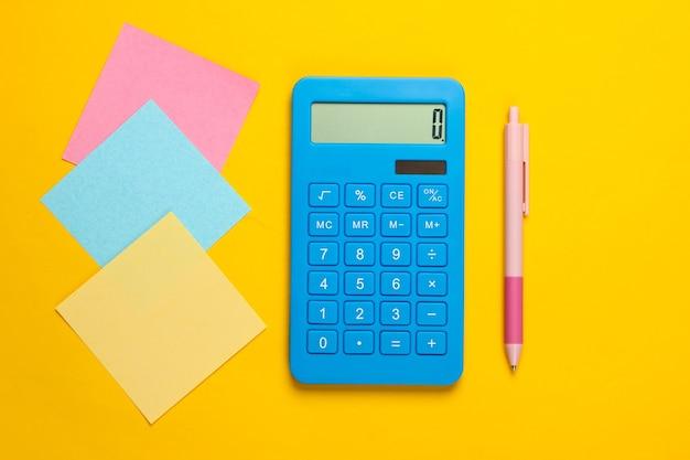 Calcolatrice blu con penna e fogli di carta appunti colorati su un giallo. strumenti di office