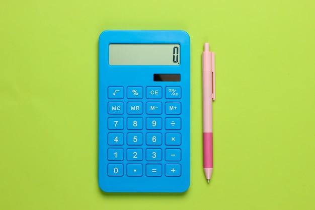 Calcolatrice blu con penna sul verde.