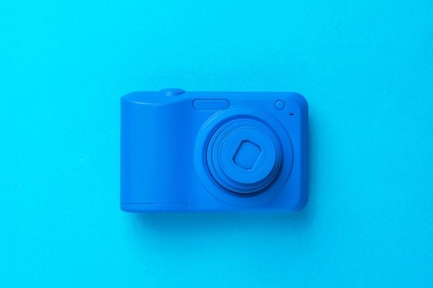 Una telecamera blu con una lente retrattile su una superficie blu. attrezzatura elegante per riprese di foto e video.