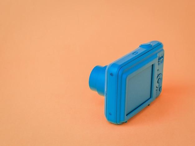 Una telecamera blu con una lente retrattile su una superficie marrone. attrezzatura elegante per riprese di foto e video.
